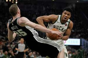 Jakob Poeltl fouls Milwaukee's Giannis Antetokounmpo, who got off to a slow start with just nine first-half points.