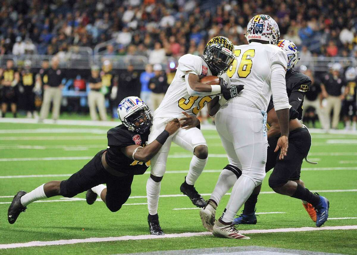 Running back DeAngelo Rosemond (39) of Team Gold drags linebacker Jadin Sommers of Team Black for a first-half score during the San Antonio Sports All-Star Football Game in the Alamodome on Saturday, Jan. 4, 2020. Rosemond attends East Central High School while Sommers attends Veterans Memorial.