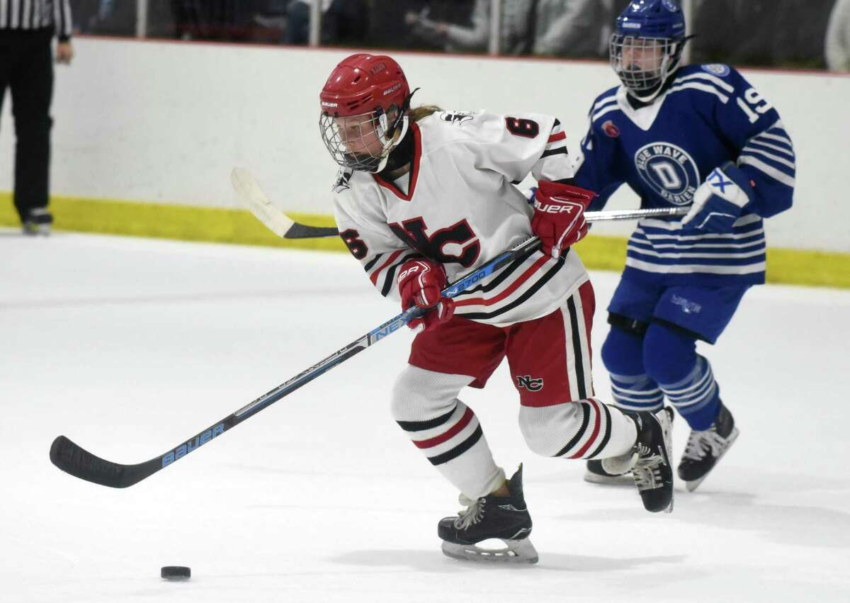 New Canaan's Jade Lowe (6) gets to the puck during a girls ice hockey game against Darien at the Darien Ice House in January.