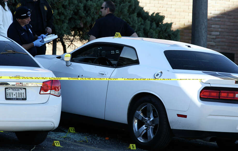 San Antonio Police investigate the scene of a double shooting at the Pecan Valley Golf Club Apartments, Sunday, Jan. 5, 2020. According to SAPD spokesperson Sgt. Michelle Ramos, two teenagers, a girl and a boy, were in a white Dodge Charger when they were shot in the parking lot of the complex. The two were taken to a local hospital, one with a wound to his leg and the girl with wounds on her back. Photo: Jerry Lara, Staff Photographer / **MANDATORY CREDIT FOR PHOTOG AND SAN ANTONIO EXPRESS-NEWS/NO SALES/MAGS OUT/TV   © 2019 San Antonio Express-News