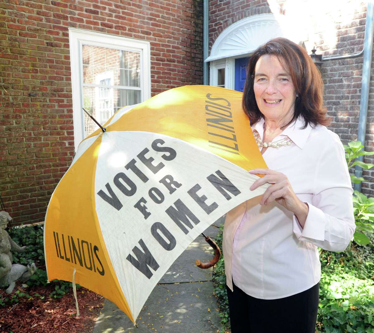 Coline Jenkins, the great-great-granddaughter of suffragette Elizabeth Cady Stanton, with an umbrella advocating the vote for women from the around the late-19th or early-20th century, at her home in Greenwich, Conn., Thursday, Oct. 6, 2016.