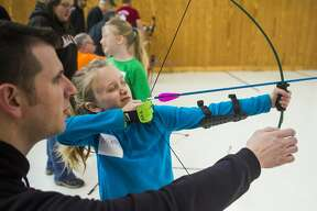 Brianna Mathews of Midland, 8, prepares to release an arrow during an archery camp for local girl scouts Saturday, Jan. 4, 2020 at Mid-Michee Bowmen in Midland. (Katy Kildee/kkildee@mdn.net)