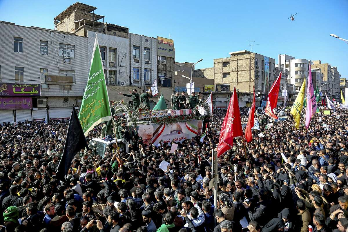 In this photo provided by the Iranian Students' News Agency, ISNA, flag draped coffins of Gen. Qassem Soleimani and his comrades who were killed in Iraq in a U.S. drone strike, carried on a truck surrounded by mourners during their funeral in southwestern city of Ahvaz, Iran, Sunday, Jan. 5, 2020. The body of Soleimani arrived Sunday in Iran to throngs of mourners, as U.S. President Donald Trump threatened to bomb 52 sites in the Islamic Republic if Tehran retaliates by attacking Americans. (Alireza Mohammadi/ISNA via AP)