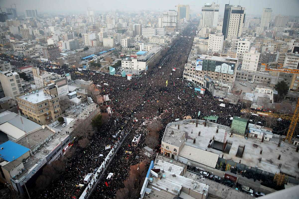 Iranians march behind a vehicle carrying the coffins of slain major general Qassem Soleimani and others as they pay homage in the northeastern city of Mashhad on January 5, 2020. - Iran has cancelled a Tehran ceremony to honour slain general Qasem Soleimani due to an overwhelming turnout by mourners in second city Mashhad, the Revolutionary Guards said. (Photo by MOHAMMAD TAGHI / TASNIM NEWS / AFP) (Photo by MOHAMMAD TAGHI/TASNIM NEWS/AFP via Getty Images)