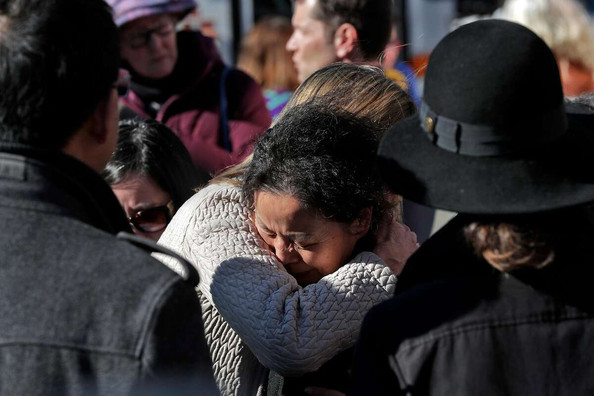 A family member of Shuo Zeng, hugs Michelle Munson during a vigil for Zeng, a 34-year-old physics specialist who died on New Year's Eve after his laptop was stolen while working at Starbucks in the Montclair neighborhood of Oakland Calif., on Sunday, January 5, 2020. Munson founded Aspera, the company that would eventually hire Zeng before he was killed when he tried to stop those who stole his laptop and he was injured in the process.