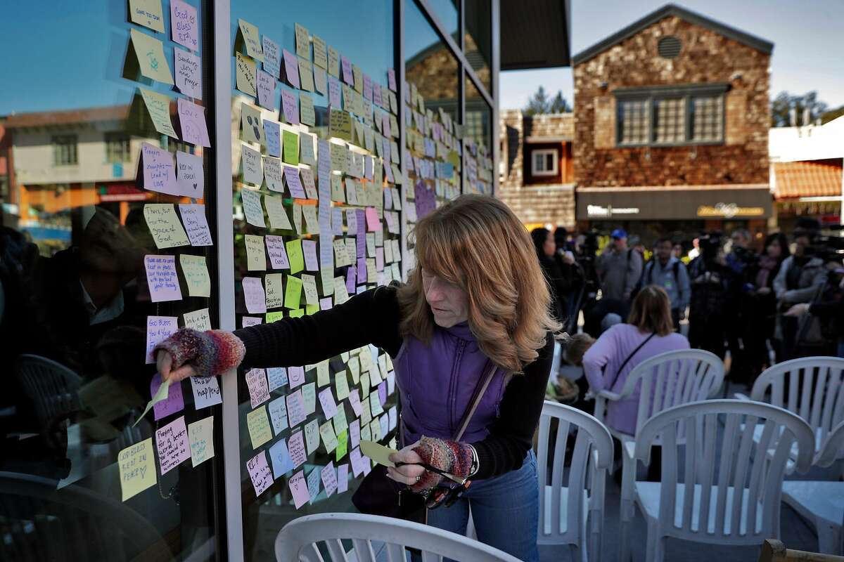 Sue Graham, posts more messages on post-it notes on a memorial for Shuo Zeng before a vigil for the 34-year-old physics specialist who died on New Year's Eve after his laptop was stolen while working at Starbucks in the Montclair neighborhood of Oakland Calif., on Sunday, January 5, 2020. Zeng was killed when he tried to stop those who stole his laptop and he was injured in the process.