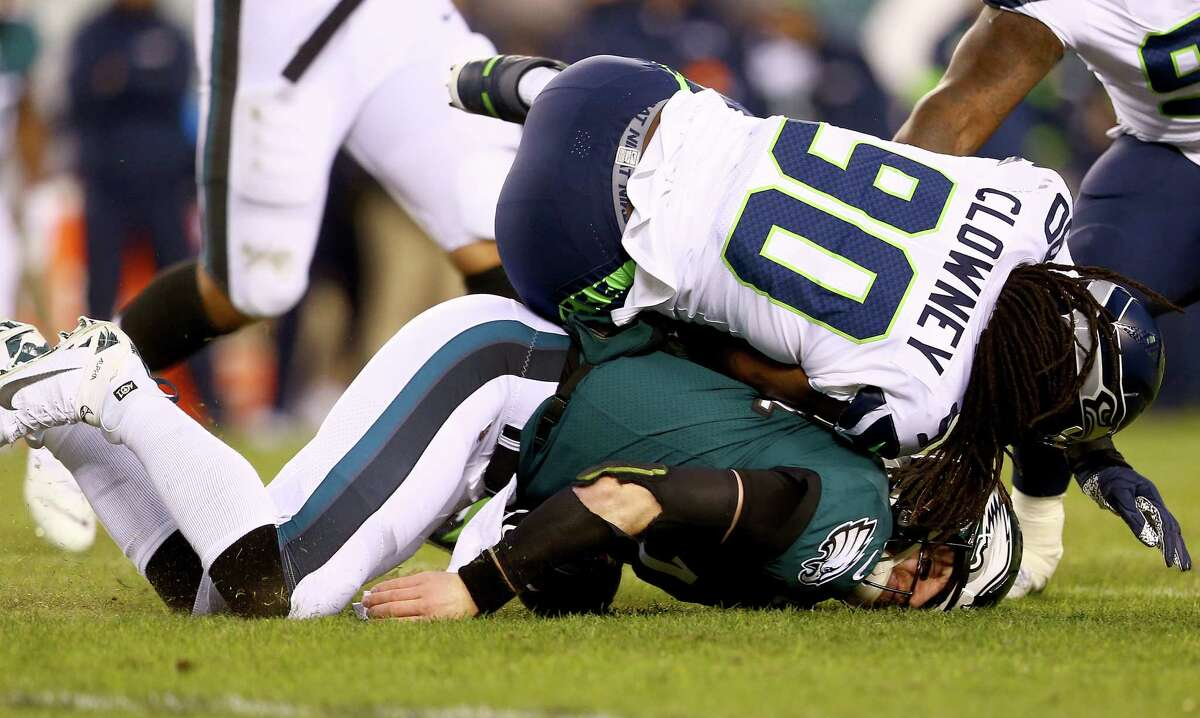 PHILADELPHIA, PENNSYLVANIA - JANUARY 05: Quarterback Carson Wentz #11 of the Philadelphia Eagles is hit by Jadeveon Clowney #90 of the Seattle Seahawks during the NFC Wild Card Playoff game at Lincoln Financial Field on January 05, 2020 in Philadelphia, Pennsylvania. (Photo by Mitchell Leff/Getty Images)