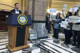 Gov. Ned Lamont answers questions from the media following a meeting of the State Bond Commission, Wednesday, Dec. 18, 2019, at the Legislative Office Building in Hartford, Conn. A group of mostly Fairfield County residents hold signs showing their support for tolls.