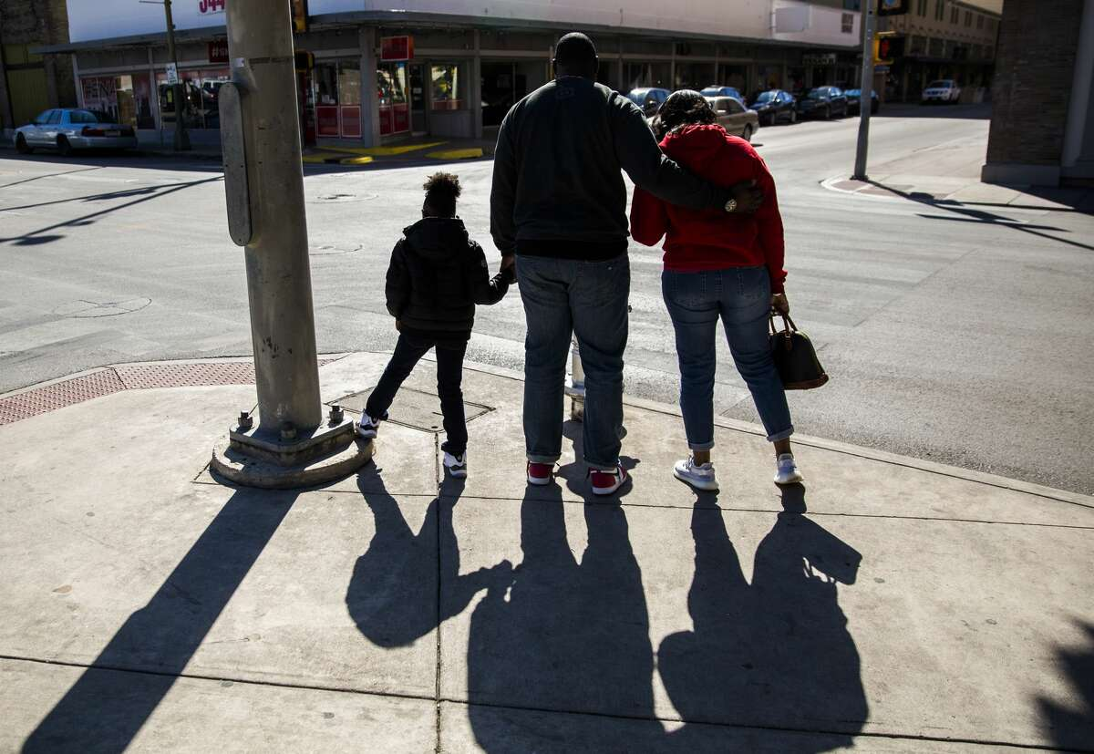 From left, Genesis Glaster, 7, and her parents, Gilbert Glaster and Crystal Glaster, wait for the light to change so they can cross the street during a family stroll downtown in San Antonio on Saturday, Nov. 2, 2019. Crystal, a lieutenant colonel in the Air Force, returned home Oct. 13 after being deployed to Pakistan for 6 months.