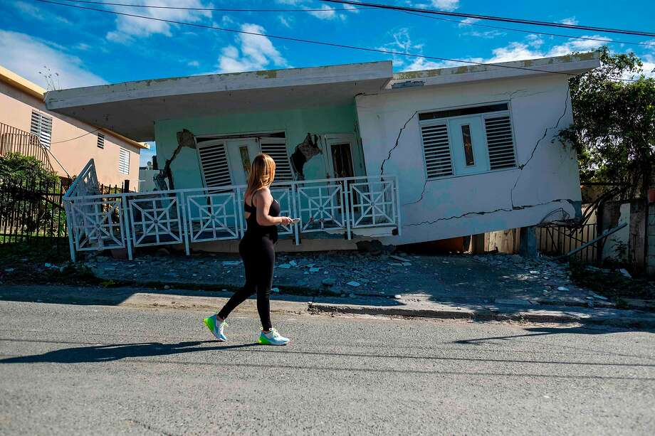 A woman passes a home in the town of Guanica in southern Puerto Rico that was heavily damaged by a 5.8 earthquake. The temblor that struck before dawn also triggered landslides. Photo: Ricardo Arduengo / AFP Via Getty Images