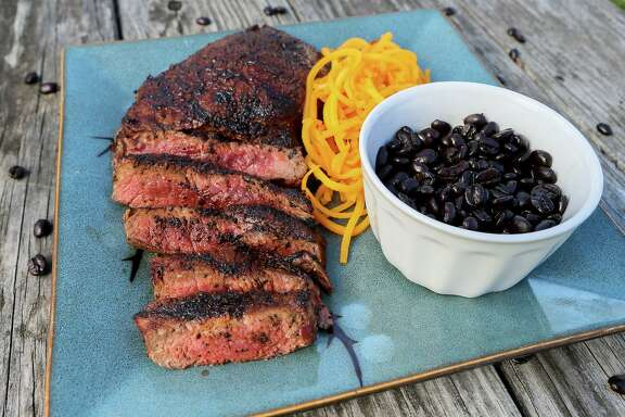 A grilled sirloin steak coated with a coffee and chile rub served with a side of squash and garnished with coffee beans.