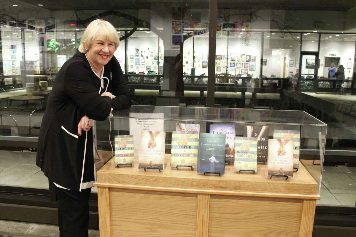 Author Heather Morris stands with a collection of her book, The Tattooist of Auschwitz, translated into many languages. Morris visited Wilton Library on April 11, 2019, to discuss her book, last year's Wilton Reads selection.