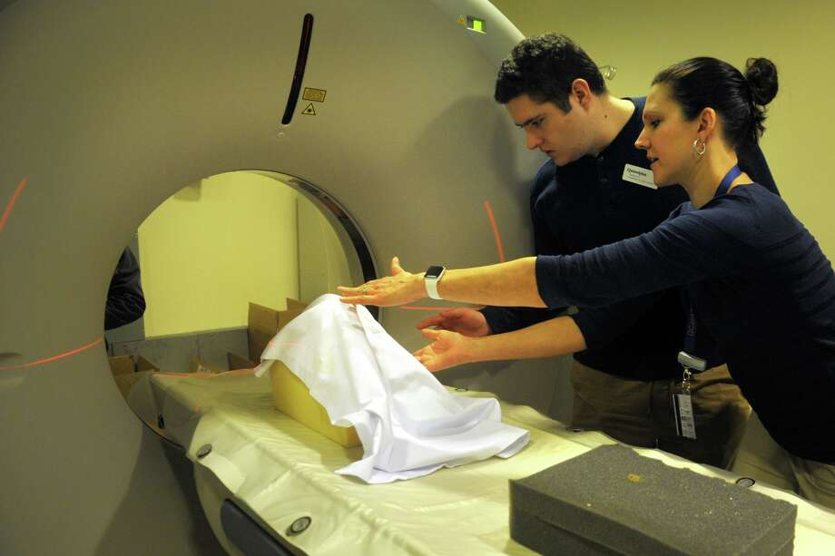 Tania Grgurich, right, clinical associate professor of diagnostic imagining, places a recentlty unearthed human skull, seen here covered by a cloth, into position in preparation for a CT scan at Quinnipiac University. She works with science student Zachary Gurahian, of Westport. Photo: Ned Gerard / Hearst Connecticut Media / Connecticut Post