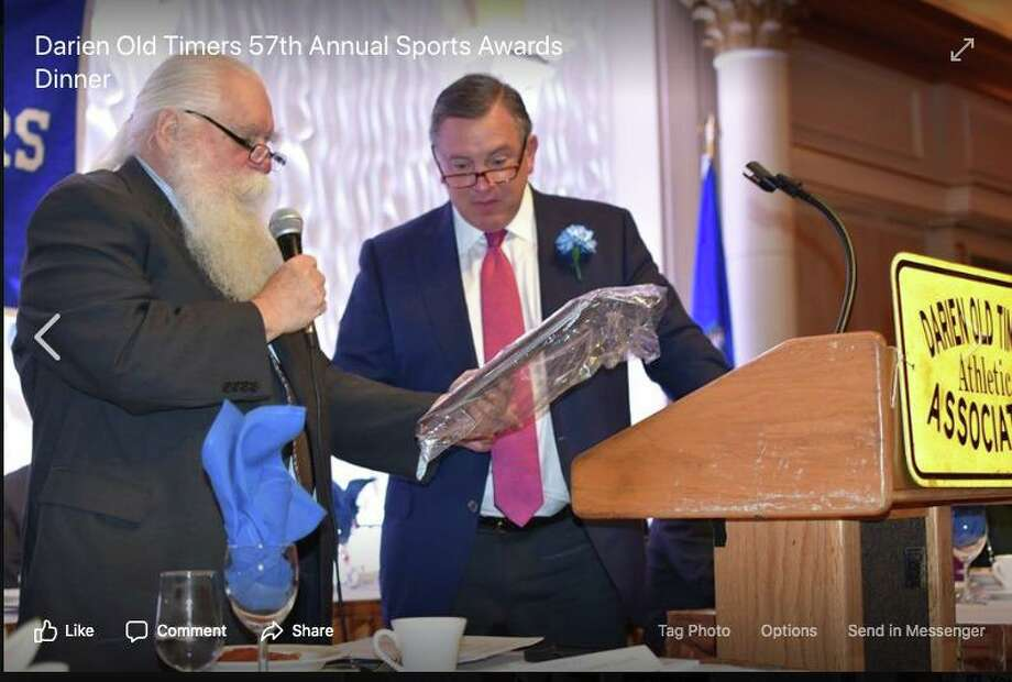 Darien Old Timers Athletic Association President Joe Warren presents an award to Mac Budd, coach of the Darien High School Hockey Team, at the 2018 sports awards dinner. Photo: Contributed Photo / / Connecticut Post