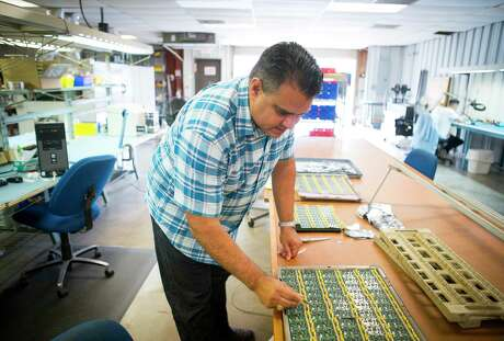 Damien Garza, president of Electronic Services Unlimited, Inc., points out the bluetooth technology added to an electronic component that the company builds in their facility in the Spring Branch area of Houston.