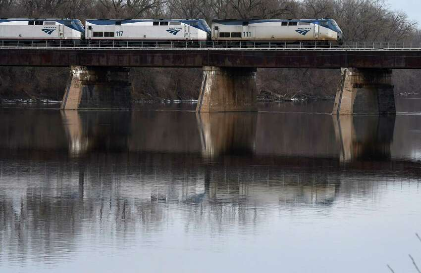An Amtrak train crosses the Mohawk River from Scotia on Monday, Jan. 6, 2020, in the Stockade neighborhood of Schenectady, N.Y. The state on Monday proposed a massive overhaul of the Erie Canal that would see ice breakers put to use to break up the ice that frequently clogs the river. (Will Waldron/Times Union)