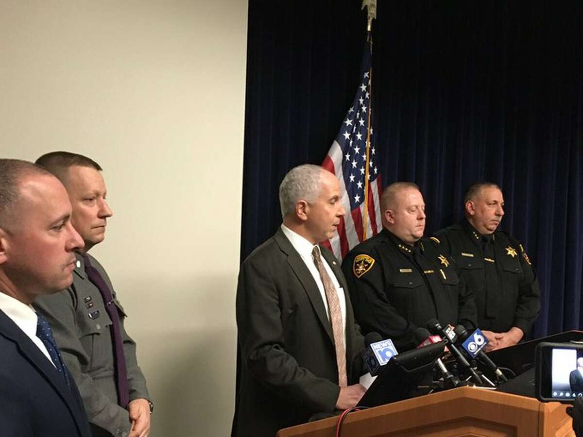 Captain Richard O'Brien of the Bureau of Criminal Investigation, center, speaks to reporters Monday about the death of a town of Mohawk man who State Police said was shot by his son.