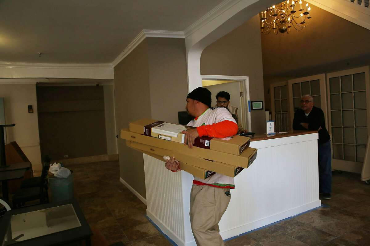 Artemio Diaz (l to r), laborer 3 Mac, carries supplies through the lobby while Alpesh Parek, front desk, and Dave Patel, manager, work together at the front desk at the Abigail Hotel on Monday, January 6, 2020 in San Francisco, Calif.