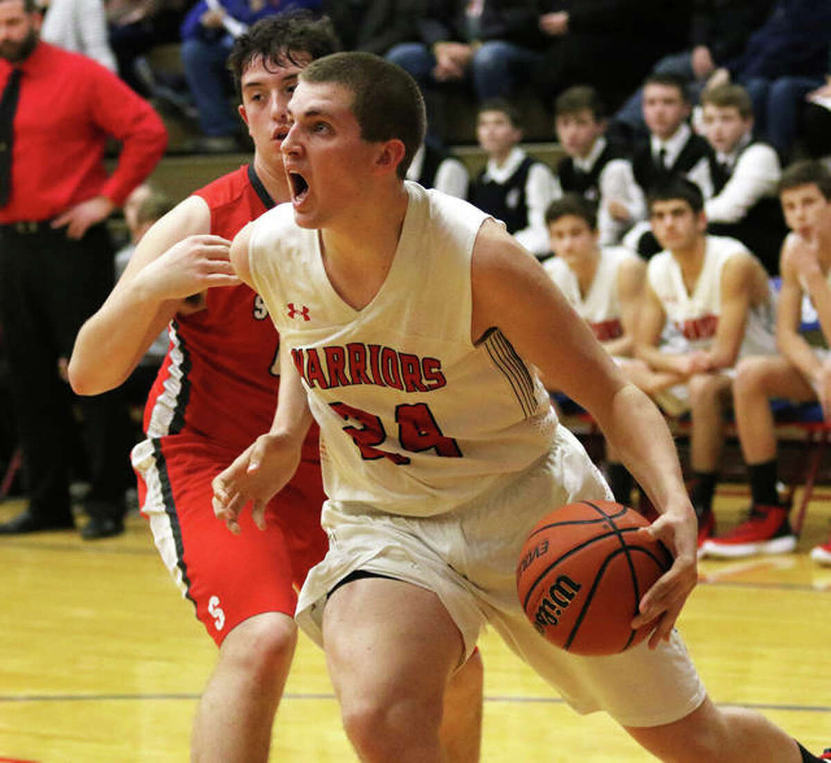 Calhoun's Ben Eberlin (24) drives baseline on Staunton's Frank Goss in a Warriors win Dec. 30 at the Carlinville Holiday Tournament.