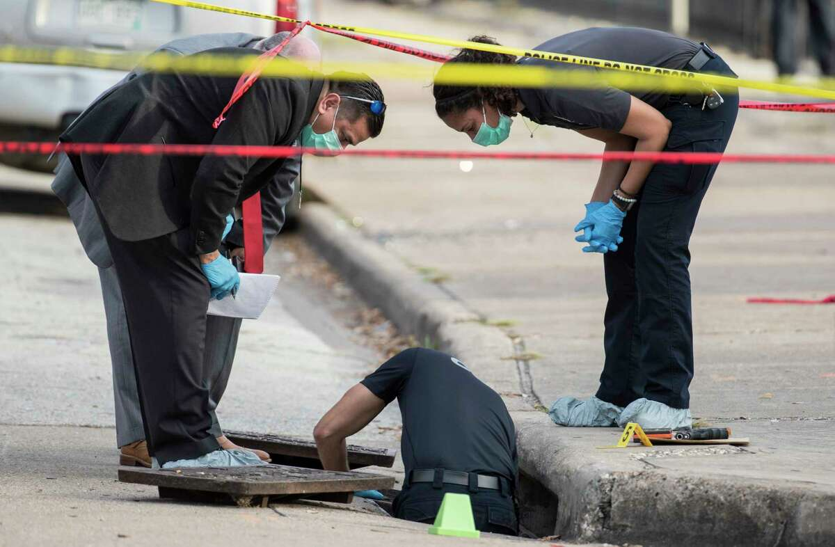 Crime Scene Unit officers investigate the scene of an officer-involved shooting near the intersection of Fannin and Hadley on Monday, Jan. 6, 2020, in Houston. An off-duty Houston police sergeant working an extra job at a Midtown business opened fire on a man who was pistol-whipping and robbing a homeless person across the street Monday afternoon, police said. The suspect threw the gun into a storm drain and fled on foot and got into a waiting car, which police believe took him to the hospital.