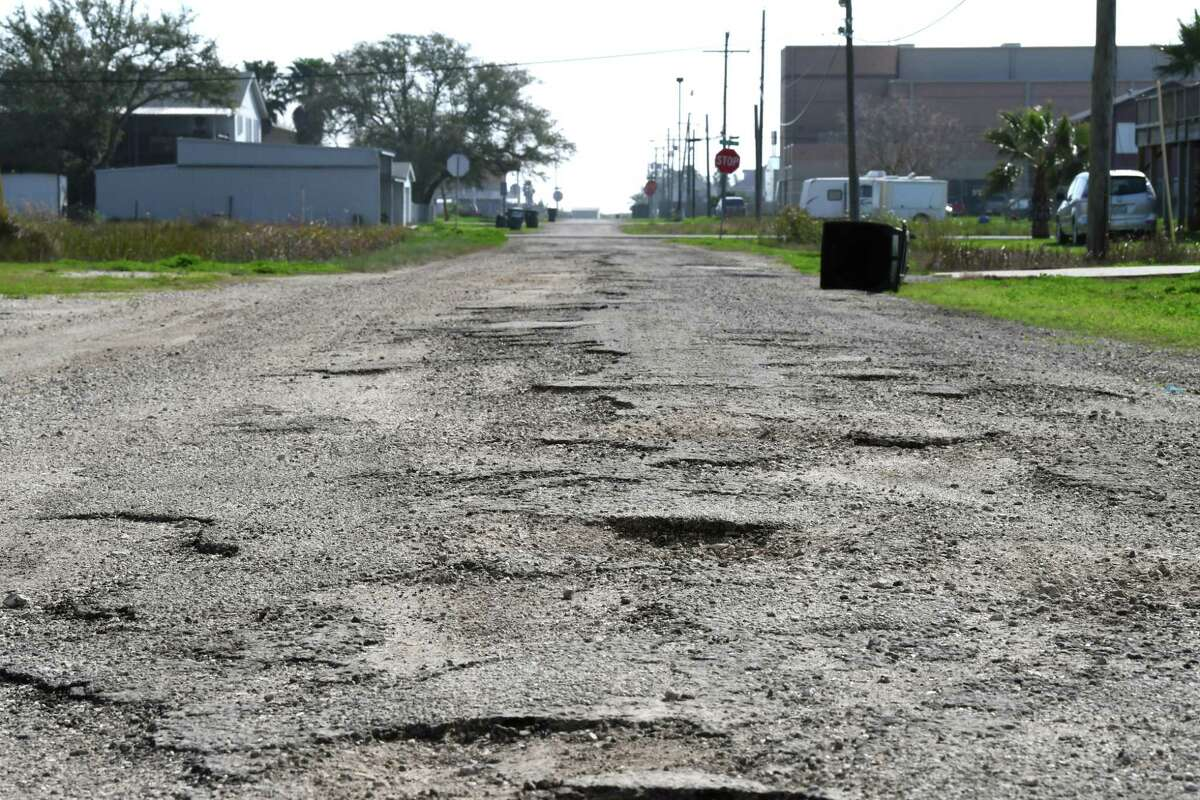 Pot holes litter Sabine Pass's 9th Avenue on Thursday. Residents of the coastal community say neglected roads are a major problem in the area. Sabine Pass school can be seen in the background. Photo taken Thursday, 2/7/19