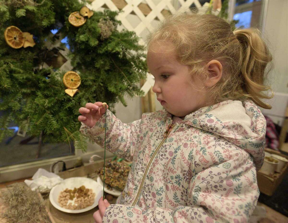 Elizabeth Arton, 3, of Wilton, threads a piece of cereal onto a wire while building a wreath during a workshop at Woodcock Nature Center on Friday evening. People were able to build wreaths for animals with food and nesting materials attached.