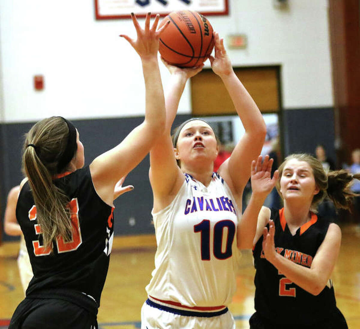 Carlinville's Elise Baker (10) puts up a shot between Gillespie's Mikala Hayes (left) and Hannah Barrett during a Dec. 30 game at the Carlinville Holiday Tourney.