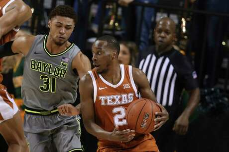 Texas guard Matt Coleman III, right, looks to pass around Baylor guard MaCio Teague, left, in the second half of an NCAA college basketball game, Saturday, Jan. 4, 2020, in Waco, Texas. (AP Photo/Rod Aydelotte)