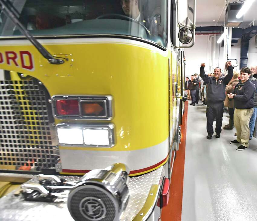 Branford, Connecticut - Monday, January 6, 2020: Firefighter / EMT David Falcigno of Indian Neck Pine POrchard Engine Co. 9 joyfully raises his hands as a firetruck backs into the new Indian Neck Pine Orchard Co. 9 firehouse as the Town of Branford Fire Department celebrates their new firehouse Monday evening with a ribbon cutting ceremony. The firehouse is home to 14 volunteer firefighters.
