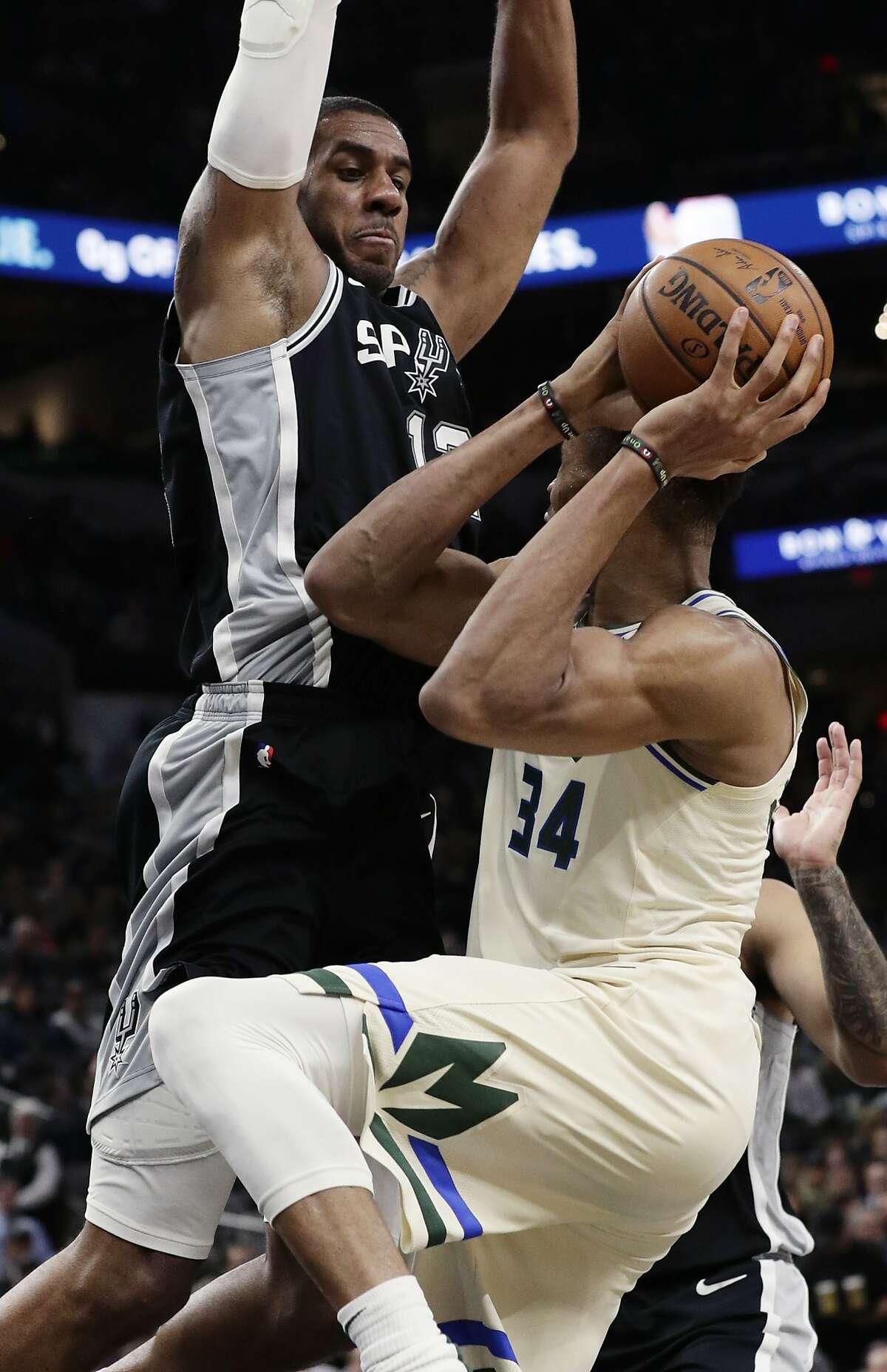 San Antonio Spurs center LaMarcus Aldridge (12) pressures Milwaukee Bucks forward Giannis Antetokounmpo (34) during the second half of an NBA basketball game, in San Antonio, Monday, Jan. 6, 2020. (AP Photo/Eric Gay)