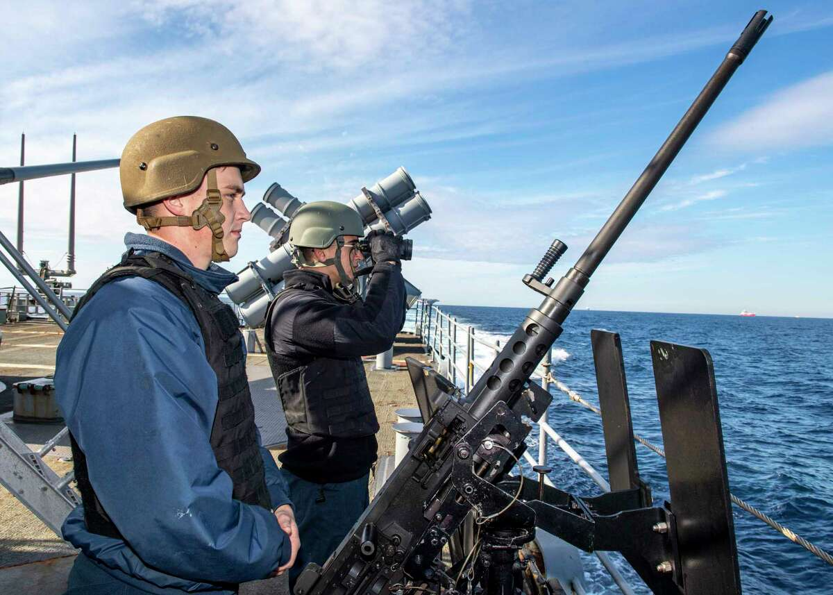 STRAIT OF GIBRALTAR - Sonar Technician (Surface) 2nd Class Davis Schaefer, front, and Sonar Technician (Surface) Seaman Isaiah Garcia, both from Houston, man a small-caliber action team as the Ticonderoga-class guided-missile cruiser USS Normandy (CG 60) transits the Strait of Gibraltar, Dec. 5, 2019. The Normandy is a part of the Harry S. Truman Carrier Strike Group (CSG) and is conducting operations in U.S. 6th Fleet to support maritime security operations in international waters, alongside our allies and partners. The Harry S. Truman CSG last operated in the U.S. 6th Fleet area of operations in 2018, demonstrating its ability to operate from the High North to the East Mediterranean.