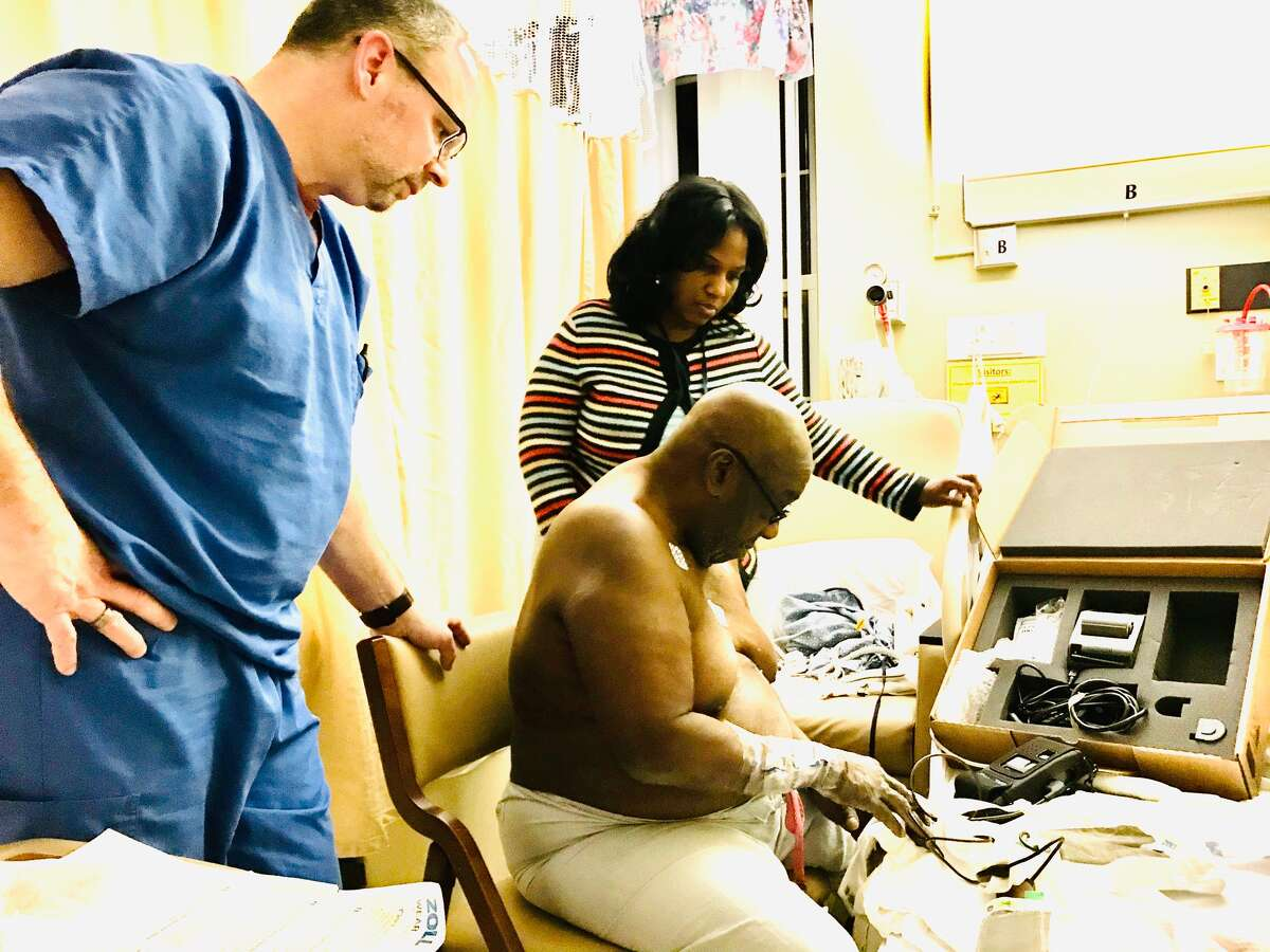 A technician and Monifa Johnson help Leon Van Dyke learn how to work his LifeVest, a heart monitoring device.