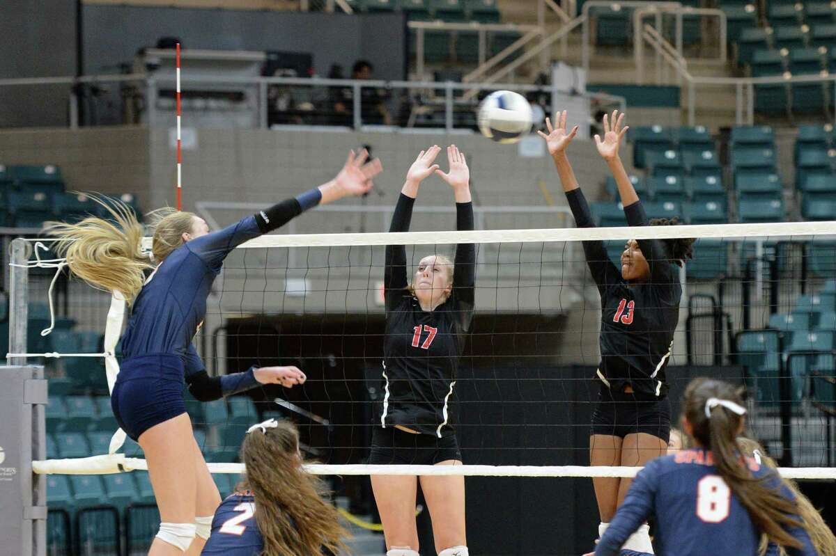 Sydney Piemons (17) and Gabby Johnson (13) of Austin try to defend a shot being made by Ally Batenhorst (14) of Seven Lakes during the first set of a Class 6A Region III bi-district volleyball playoff match between the Seven Lakes Spartans and the Ft. Bend Austin Bulldogs on Tuesday, November 5, 2019 at the Leonard Merrell Center, Katy, TX.