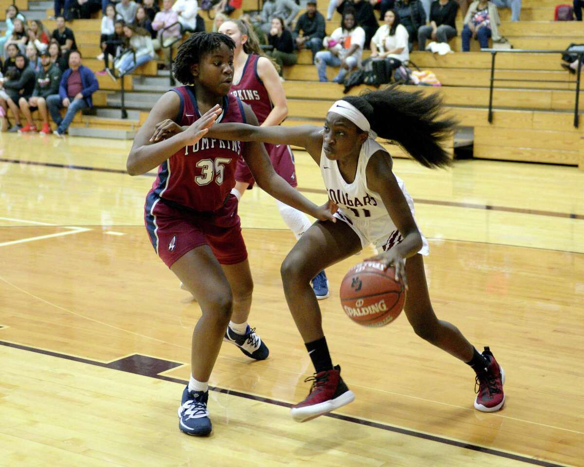 Peniel Otto (11) of Cinco Ranch drives past Fiyin Adeleye (35) of Tompkins during the first quarter of a 6A Region III District 19 Girls basketball game between the Cinco Ranch Cougars and the Tompkins Falcons on Friday, January 3, 2020 at Cinco Ranch HS, Katy, TX.