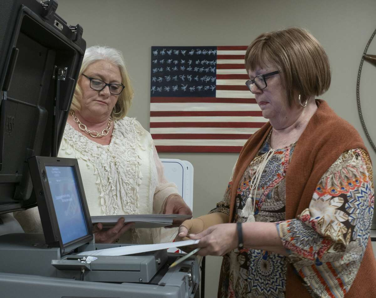 Carolyn Grays, right, feeds one ballot at a time as she and Beth Shock test the DS200 01/07/20 during testing of ballot machines at the Midland County Elections office. Tim Fischer/Reporter-Telegram