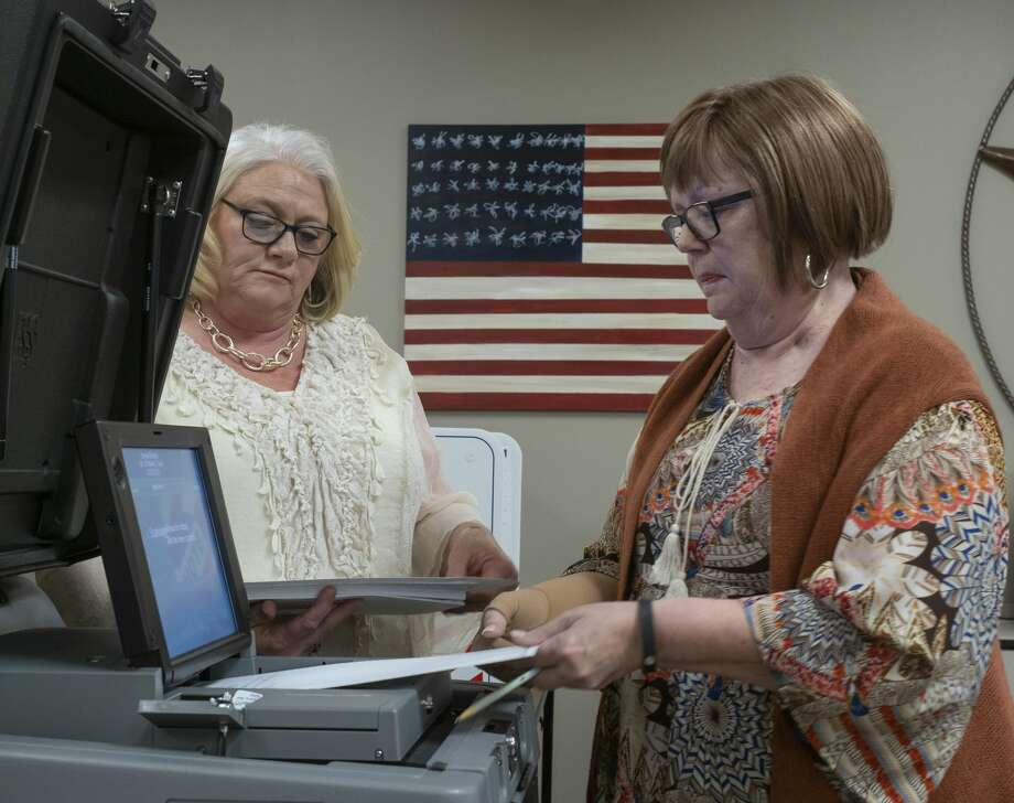 Carolyn Grays, right, feeds one ballot at a time as she and Beth Shock test the DS200 01/07/20 during testing of ballot machines at the Midland County Elections office. Tim Fischer/Reporter-Telegram Photo: Tim Fischer/Midland Reporter-Telegram