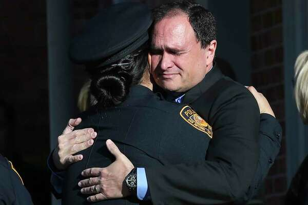 """People hug outside the Porter Loring Mortuary before a funeral procession for SAISD Det. Clifton J. """"Cliff"""" Martinez on Tuesday. A 28-year veteran with the district, he was killed early Dec. 21 as he attempted to break up a fight between two men while working security for a Southeast Side restaurant, according to San Antonio police."""