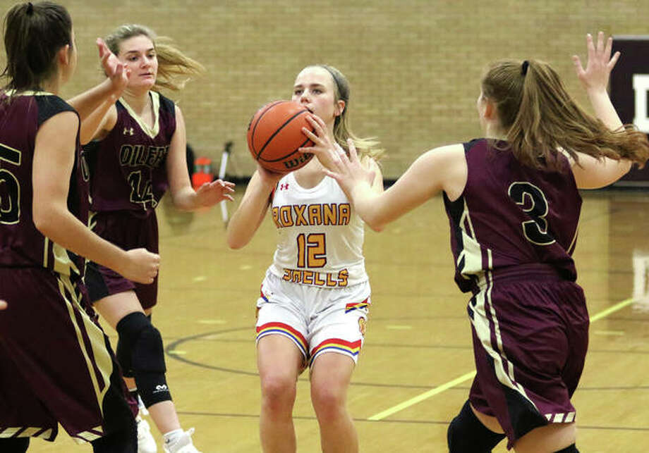 Roxana's Olivia Mouser (12) pulls up for a shot between EA-WR's Karli Withers (3), Aubrey Robinson (second left) and Hannah Allen in a Nov. 19 game at the Dupo Tourney. The Shells and Oilers met again Monday night in Wood River and Mouser led all scorers with eight points in EA-WR's win. Photo: Greg Shashack / The Telegraph