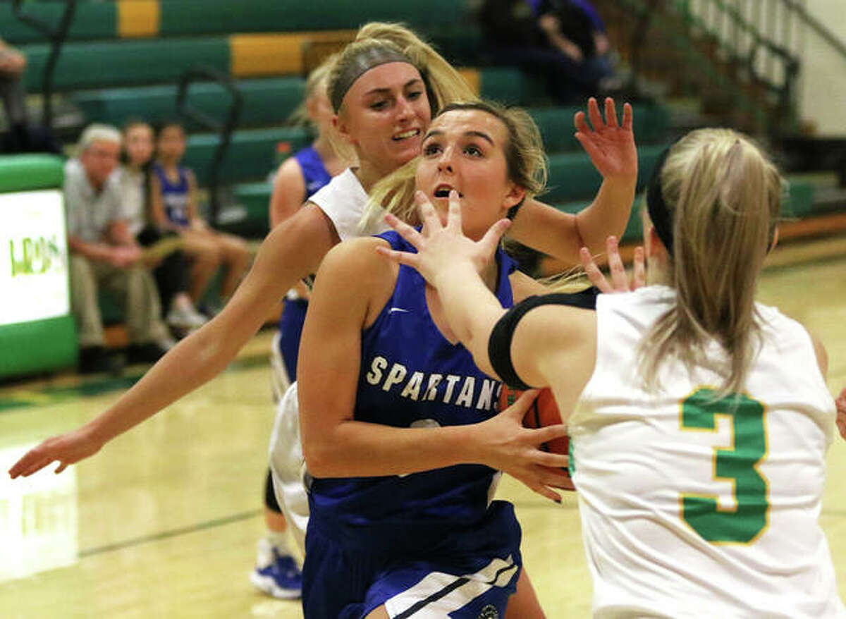 North Greene's Lakeleigh Brown (middle) looks to the basket after splitting Southwestern defenders Morgan Durham and Addie Green (3) in a Nov. 20 game in Piasa. On Monday, Brown scored 31 points in a Spartans' win at South Fork.