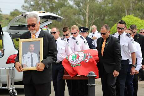 New South Wales Rural Fire Service crew members from Horsley Park RFS carry the casket of NSW RFS volunteer Andrew O'Dwyer during his funeral service at Our Lady of Victories Catholic Church in Horsley Park, Sydney, Tuesday, Jan. 7, 2020. O'Dwyer, 36, and RFS colleague Geoffrey Keaton were killed six days before Christmas when a tree fell in the path of their truck at the still-burning Green Wattle Creek fire, causing it to roll.