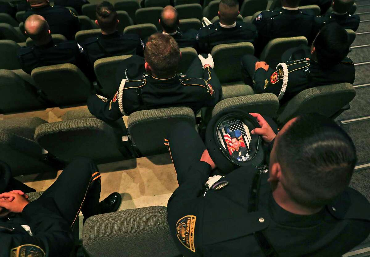 A member of the Honor Guard from the Corpus Christi Police Department looks at the photo of Det. Cliff Martinez on the funeral program he placed in his hat, during the service for the SAISD officer held at Community Bible Church.