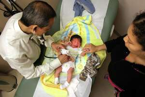 Jessica Galan, right, 21 yrs old, holds the hand of her 3-day old son Jonathan Sauceda as Dr. Melanio P. Villarosa II, left, checks on his condition at the New Horizon Medical Center which is part of Brownsville Community Health Center. Galan has 3 other kids. Affordable health care in the Rio Grande Valley is hard to come by. Tuesday, May 15, 2012. Photo/Bob Owen