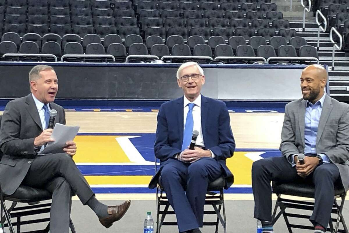 Wisconsin Gov. Tony Evers, center, and Lt. Gov. Mandela Barnes, right, take questions Tuesday, Jan. 7, 2020 from Democratic National Convention chief officer Joe Solmonese, left,on the floor of the Fiserv Forum in Milwaukee at a media walk-through event six months before the convention kicks off in July. (AP Photo/Scott Bauer)
