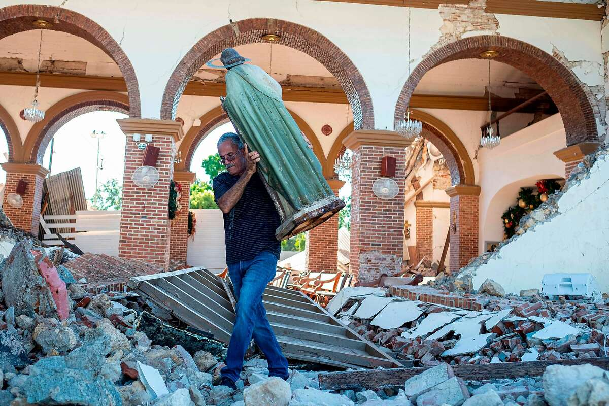 A man carries a St. Jude statue from the Inmaculada Concepcion church ruins that was built in 1841 and collapsed after an earthquake hit the island in Guayanilla, Puerto Rico on January 7, 2020. - A strong earthquake struck south of Puerto Rico early January 7, 2020 followed by major aftershocks, the US Geological Survey said, the latest in a series of tremors that have shaken the island since December 28. The shallow 6.4 magnitude quake struck five miles (eight kilometers) south of the community of Indios, the USGS said, revising down its initial reading of 6.6.