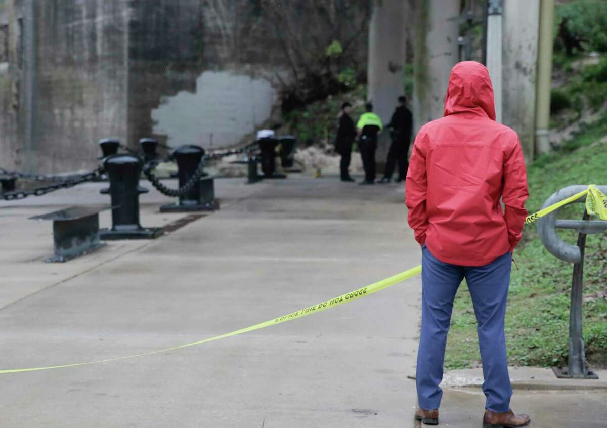 An onlooker who thinks he knows the victims watches as the Houston Police pull out a body discovered in the Buffalo Bayou on Thursday, Jan. 2, 2020 in Houston.