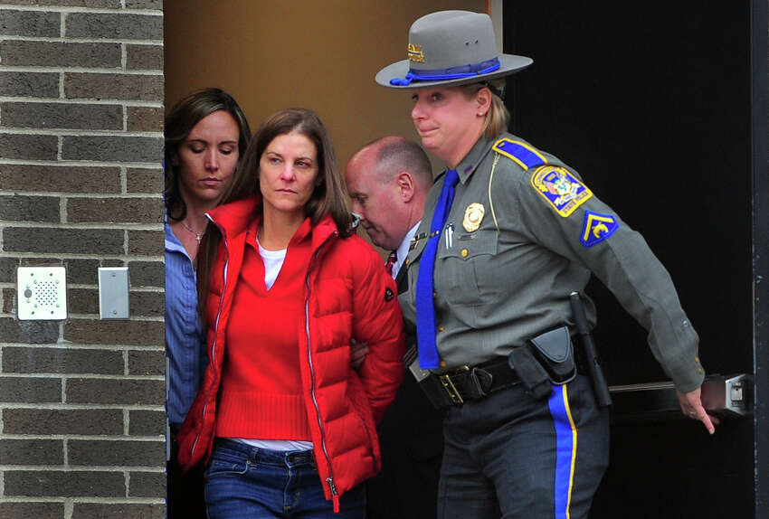 Michelle Troconis is escorted to an awating police vehicle after being arrested and processed at State Police Troop G Headquarters in Bridgeport, Conn., on Tuesday Jan. 7, 2020.