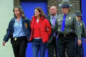 Michelle Troconis is escorted to an awating police vehicle after being arrested and processed at State Police Troop G Headquarters in Bridgeport on Tuesday, January 7, 2020.