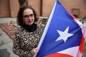 Micky Jimenez, executive director of Capital District Latinos, holds a Puerto Rican flag on Tuesday, Jan. 7, 2020, outside her Central Avenue offices in Albany, N.Y. Jimenez lost contact with her brother, Jorge Hernandez, after the Caribbean island was struck by earthquakes. (Will Waldron/Times Union)