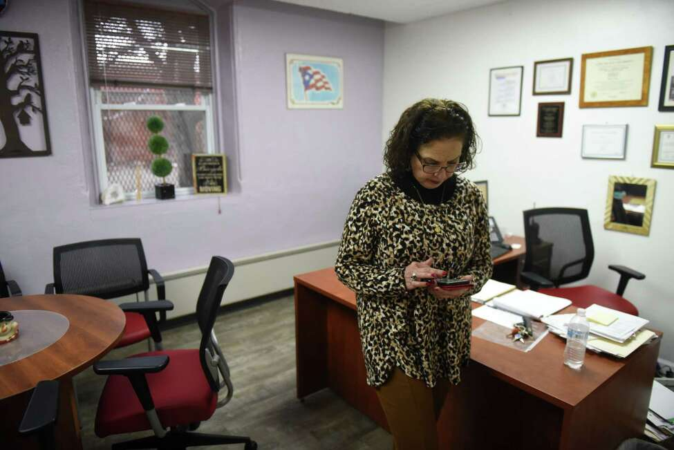 Micky Jimenez, executive director of Capital District Latinos, searches for a photo of her brother, Jorge Hernandez, on Tuesday, Jan. 7, 2020, at her Central Avenue offices in Albany, N.Y. Jimenez lost contact with her sibling after the Caribbean island was struck by earthquakes. (Will Waldron/Times Union)
