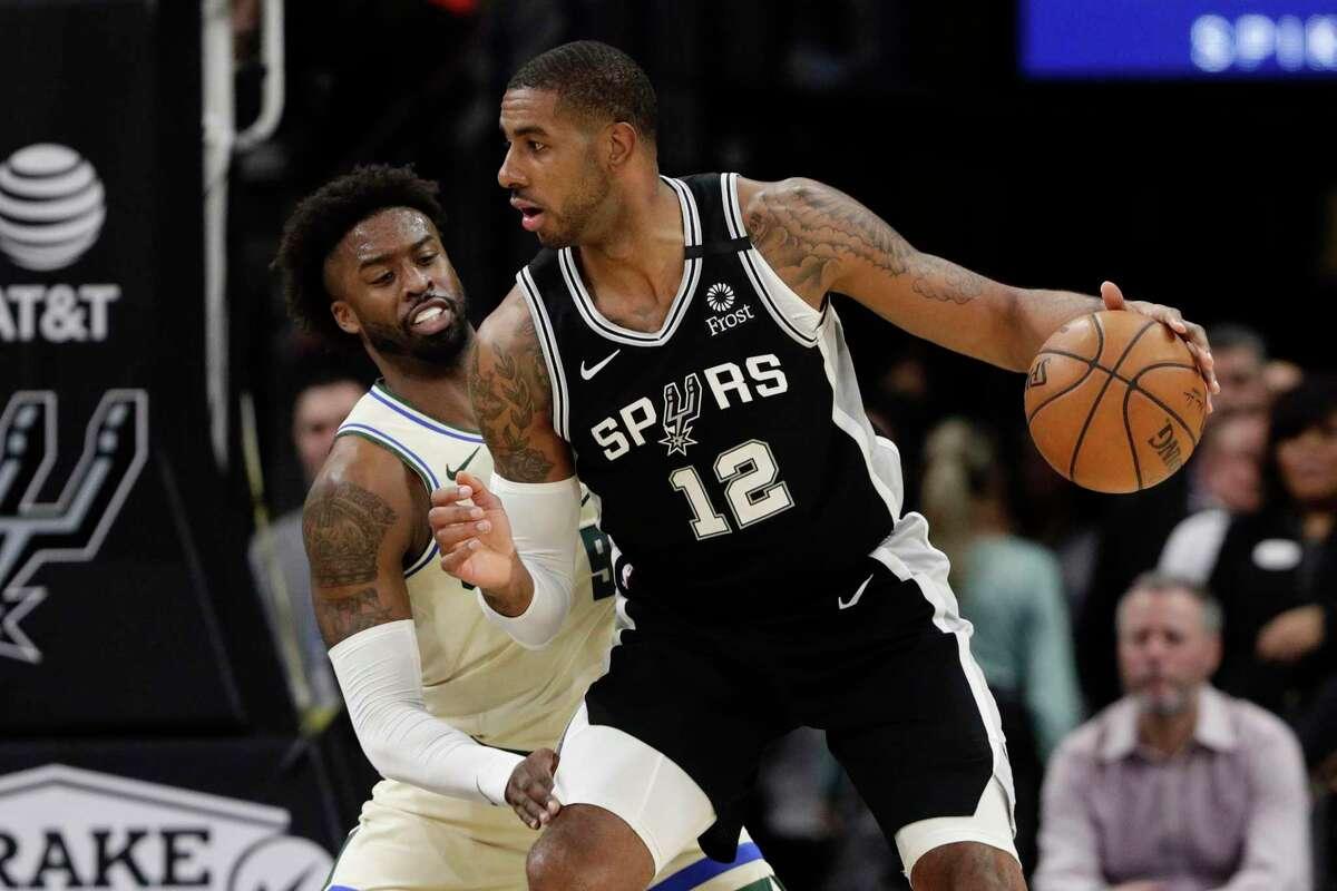 San Antonio Spurs center LaMarcus Aldridge (12) drives around Milwaukee Bucks guard Wesley Matthews (9) during the first half of an NBA basketball game, in San Antonio, Monday, Jan. 6, 2020. (AP Photo/Eric Gay)